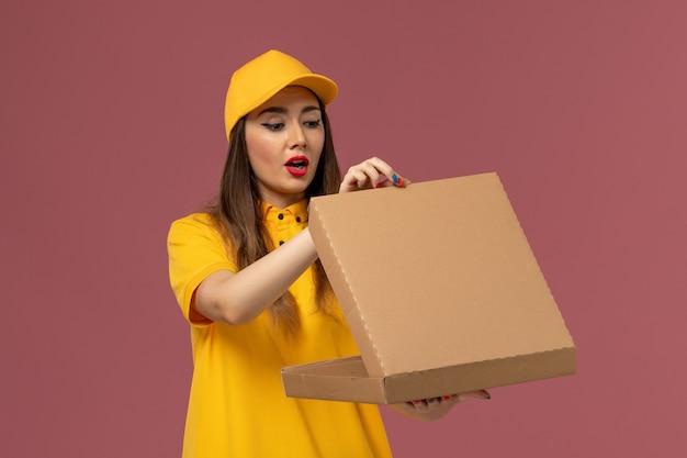 黄色のユニフォームとフードボックスを保持し、淡いピンクの壁にそれを開くキャップの女性の宅配便の正面図