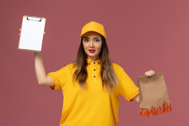 ピンクの壁に食品パッケージとメモ帳を保持している黄色の制服とキャップの女性の宅配便の正面図