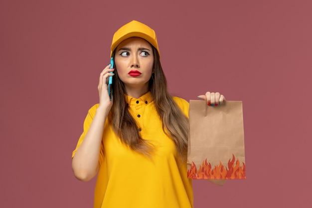 黄色の制服と帽子を保持し、ピンクの壁に電話で話している女性の宅配便の正面図