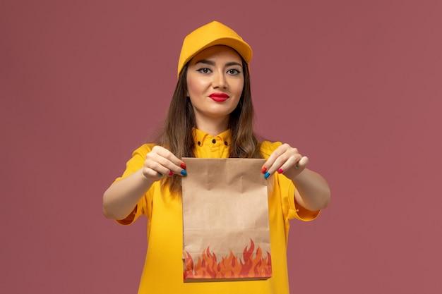 黄色のユニフォームと薄ピンクの壁に食品パッケージを保持しているキャップの女性の宅配便の正面図