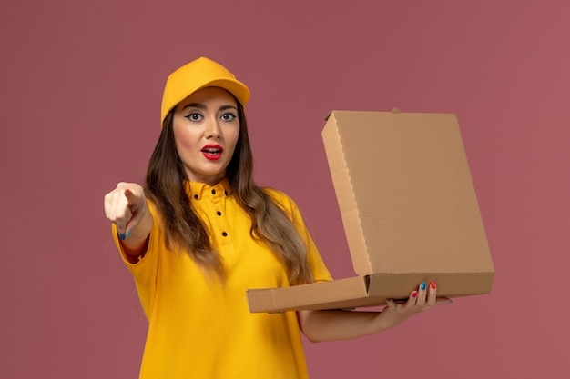 黄色のユニフォームと薄ピンクの壁に開いたフードボックスを保持しているキャップの女性の宅配便の正面図
