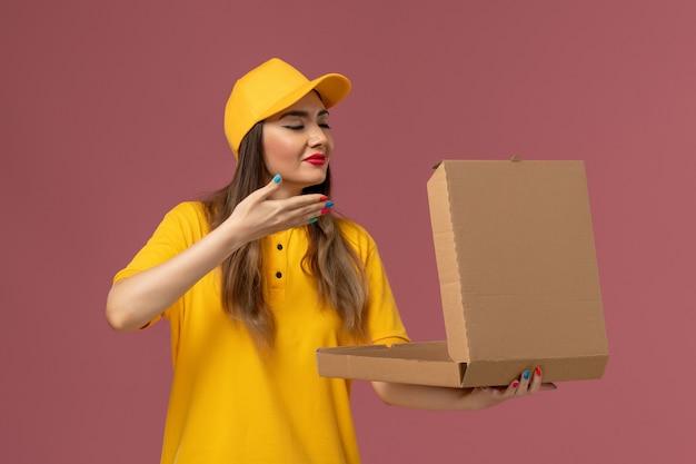 黄色の制服と薄ピンクの壁に臭いがする開いたフードボックスを保持しているキャップの女性の宅配便の正面図