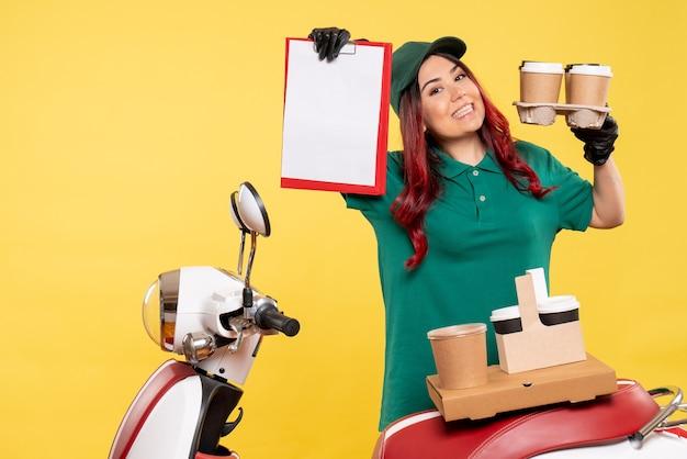 黄色の壁にファイルノートとコーヒーと女性の宅配便の正面図