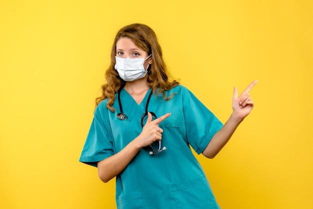 黄色の壁にマスクで女医師の正面図