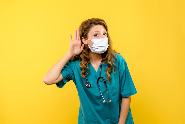 Вид спереди женщины-врача в маске на желтой стене