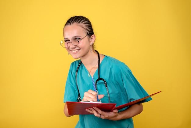 黄色の壁にメモを書いている医療シャツの女性医師の正面図