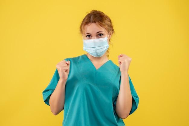 노란색 벽에 의료 소송 및 마스크 여성 의사의 전면보기