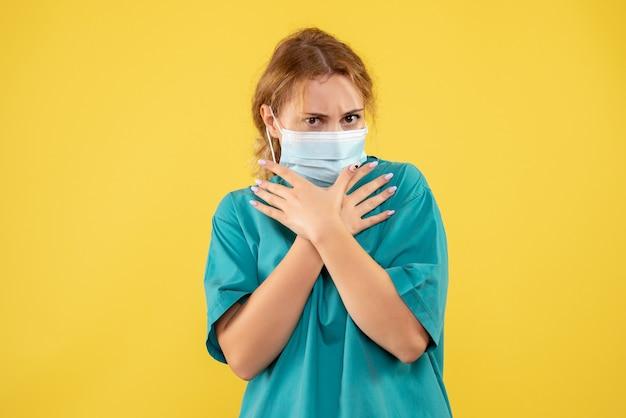黄色の壁に医療スーツとマスクの女性医師の正面図