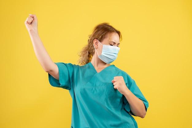 Вид спереди женщины-врача в медицинском костюме и маске на желтой стене