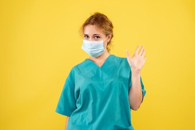 Вид спереди женщины-врача в медицинском костюме и стерильной маске на желтой стене