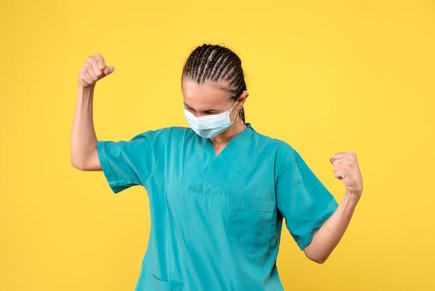 医療スーツと黄色の壁に滅菌マスクの女性医師の正面図