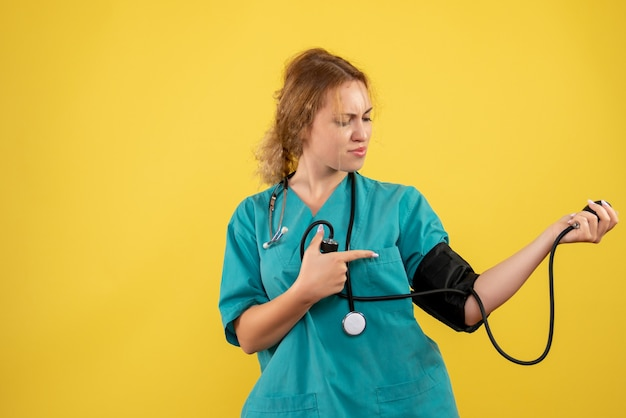 黄色い壁に彼女の圧力をチェックする医療スーツの女性医師の正面図