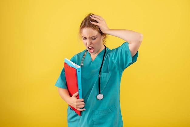 黄色の壁に異なる分析を保持している医療スーツの女性医師の正面図