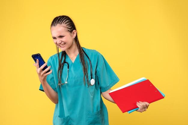 Вид спереди женщины-врача в медицинском костюме, держащей телефон на желтой стене