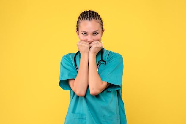黄色い壁に神経質な医療スーツを着た女性医師の正面図