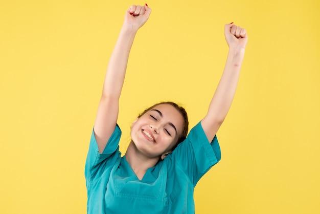 노란색 벽에 기쁨 의료 소송에서 여성 의사의 전면보기