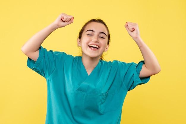 노란색 벽에 기뻐하는 얼굴로 기뻐하는 의료 소송에서 여성 의사의 전면보기