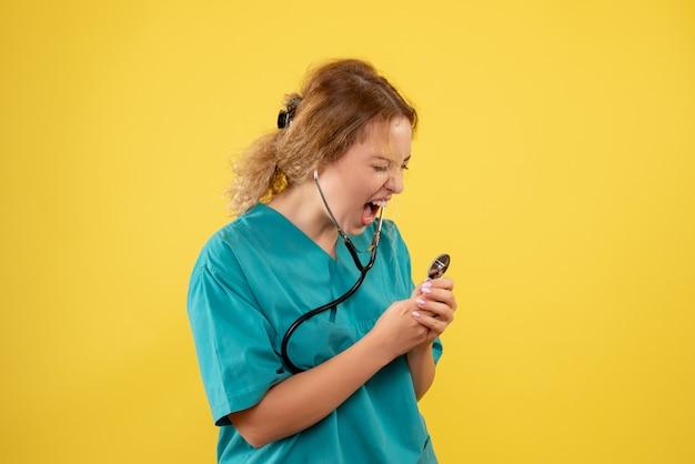 노란색 벽에 청진 기에서 비명 의료 소송에서 여성 의사의 전면보기