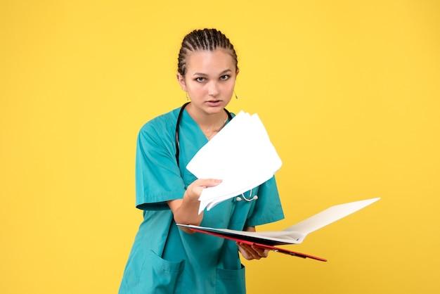 黄色の壁に異なる分析と医療スーツの女性医師の正面図