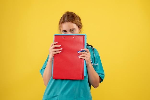 Вид спереди женщины-врача в медицинском костюме с бумагами и анализом на желтой стене
