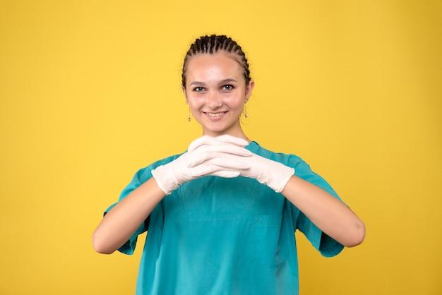 Вид спереди женщины-врача в специальных перчатках на желтой стене