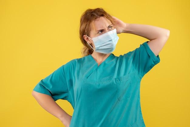 노란색 벽에 멸균 보호 마스크에 여성 의사의 전면보기