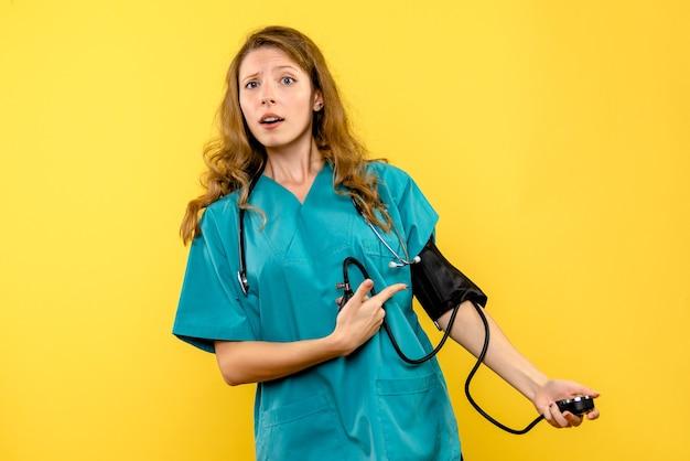 Женщина-врач, измеряющая давление на желтой стене, вид спереди
