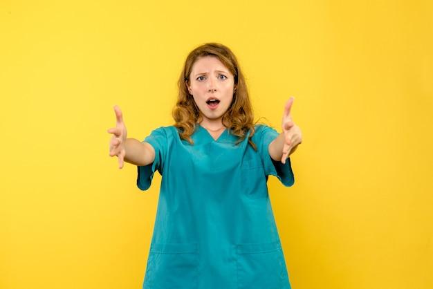 노란색 벽에 여성 의사의 전면보기