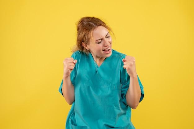 노란색 벽에 의료 셔츠에 기쁨 여성 의사의 전면보기 무료 사진