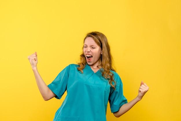 黄色い壁で喜んでいる女性医師の正面図