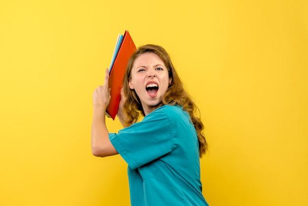 Женщина-врач, кричащая на желтой стене, вид спереди
