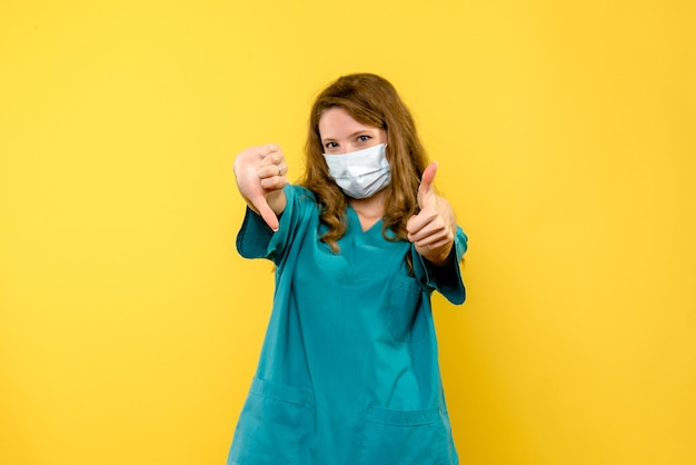 Вид спереди женщины-врача, показывающей знаки на желтой стене