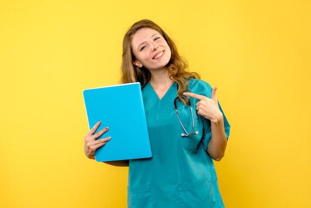 黄色の壁に笑みを浮かべて女医師の正面図