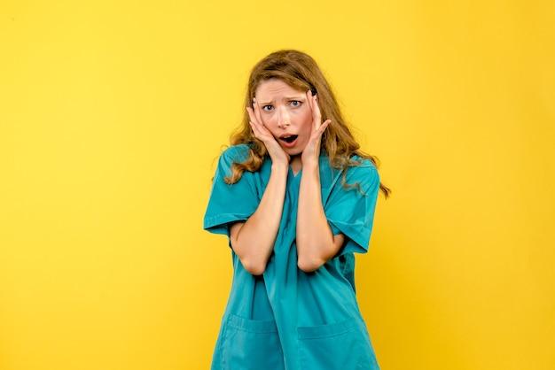 黄色い壁に強調された女医師の正面図