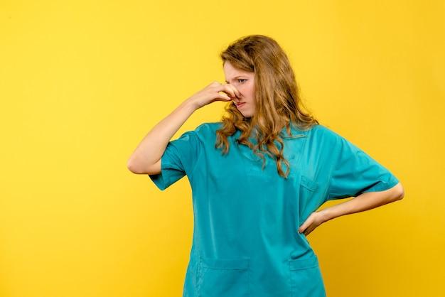 노란색 벽에 여성 의사 stucking 코의 전면보기