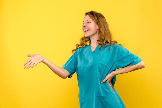 Вид спереди женщины-врача, разговаривающей с кем-то на желтой стене