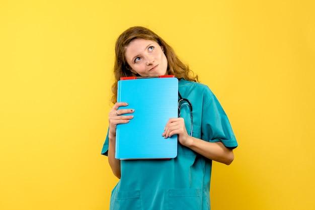노란색 벽에 분석 여성 의사의 전면보기