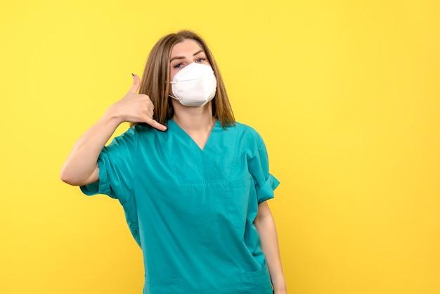 Вид спереди женщины-врача с маской на желтом полу в пандемической медицинской больнице