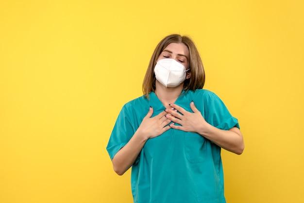 노란색 벽에 마스크와 여성 의사의 전면보기
