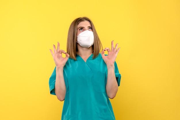 Вид спереди женщины-врача с маской на желтой стене