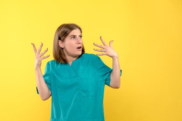 黄色い壁に驚いた表情で女医師の正面図
