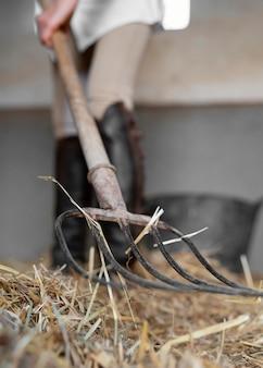 말 마구간에서 건초를 청소하는 여성 농부의 전면보기