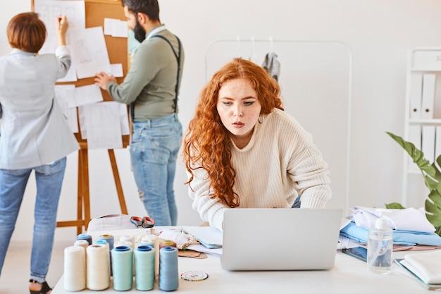Вид спереди модельера женского пола, работающего в ателье с ноутбуком и коллегами