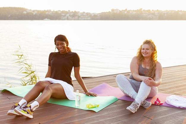 호수에서 운동 후 휴식하는 여자 친구의 전면보기