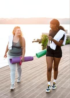 Вид спереди подруг, гуляющих по озеру с ковриками для йоги