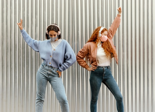 ヘッドフォンをつけて屋外で踊るフェイスマスクを持つ女性の友人の正面図
