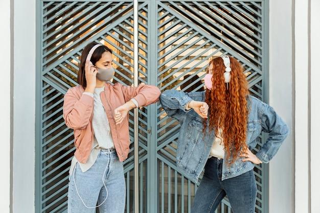 屋外で肘の敬礼をしているフェイスマスクを持つ女性の友人の正面図