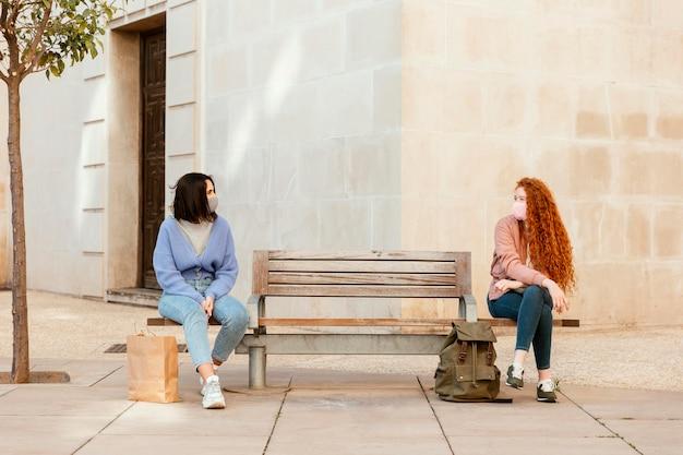 屋外のベンチに座っているフェイスマスクを持つ女性の友人の正面図