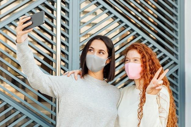 屋外で自分撮りをしているフェイスマスクを持つ女性の友人の正面図