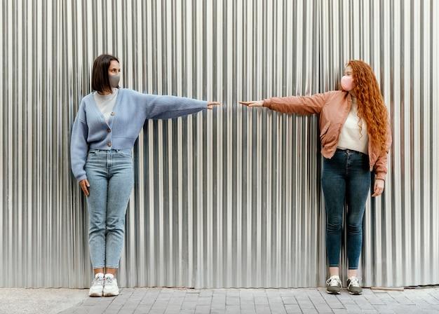 屋外で指に触れるフェイスマスクを持つ女性の友人の正面図